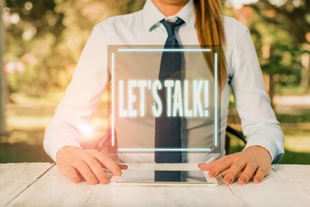Text sign showing Let S Talk. Business photo text they are suggesting beginning conversation on specific topic Female business person sitting by table and holding mobile phone