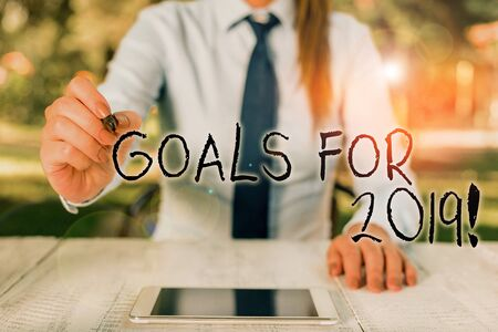 Text sign showing Goals For 2019. Business photo text object of demonstratings ambition or effort aim or desired result Female business person sitting by table and holding mobile phone