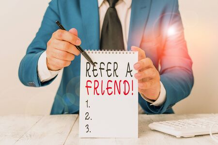 Text sign showing Refer A Friend. Business photo showcasing direct someone to another or send him something like gift Man holds empty paper with copy space in front of him Copy Space