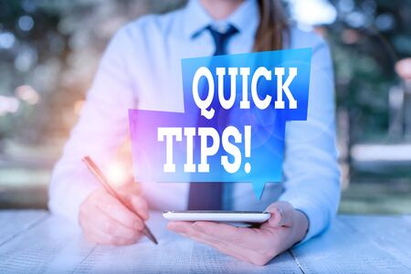 Word writing text Quick Tips. Business photo showcasing small but particularly useful piece of practical advice Female business person sitting by table and holding mobile phone