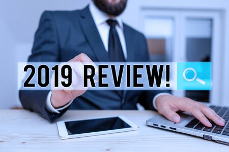 Word writing text 2019 Review. Business photo showcasing remembering past year events main actions or good shows Male human wear formal clothes present presentation use hi tech smartphone