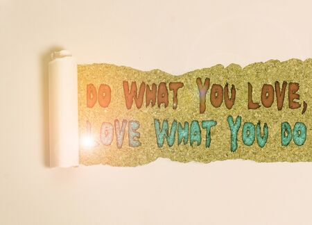 Handwriting text Do What You Love Love What You Do. Conceptual photo Pursue your dreams or passions in life Cardboard which is torn in the middle placed above a wooden classic table Banco de Imagens