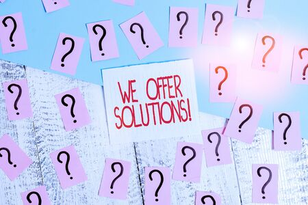 Word writing text We Offer Solutions. Business photo showcasing way to solve problem or deal with difficult situation Scribbled and crumbling papers with thick cardboard above wooden table 写真素材