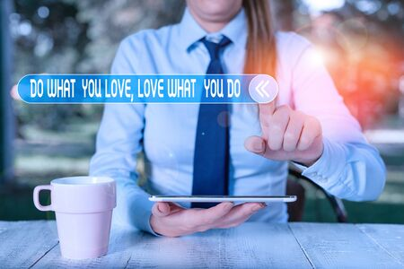 Handwriting text writing Do What You Love Love What You Do. Conceptual photo Pursue your dreams or passions in life Female business person sitting by table and holding mobile phone