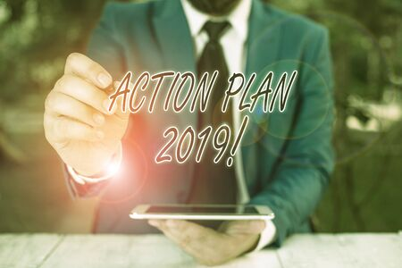 Word writing text Action Plan 2019. Business photo showcasing proposed strategy or course of actions for current year Businessman pointing with pen in empty copy space 写真素材