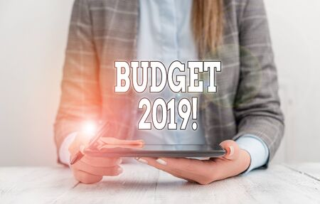 Conceptual hand writing showing Budget 2019. Concept meaning estimate of income and expenditure for current year Business woman sitting with mobile phone on the table