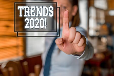 Writing note showing Trends 2020. Business concept for general direction in which something is developing or changing Blurred woman in the background pointing with finger in empty space