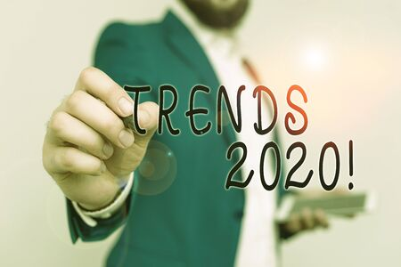 Writing note showing Trends 2020. Business concept for general direction in which something is developing or changing Businessman with pointing finger in front of him