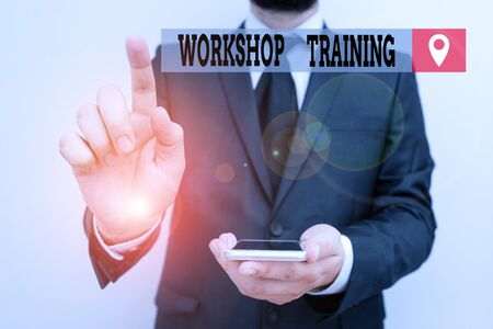 Writing note showing Workshop Training. Business concept for participants carry out a number of training activities Male human wear formal work suit hold smartphone using hand