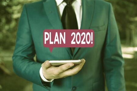Text sign showing Plan 2020. Business photo text detailed proposal doing achieving something next year Businessman in blue suite stands with mobile phone in hands