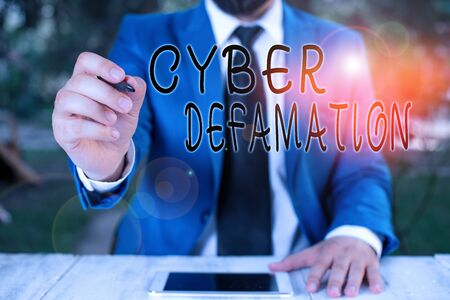Conceptual hand writing showing Cyber Defamation. Concept meaning slander conducted via digital media usually by Internet Businessman holds pen and points into copy space