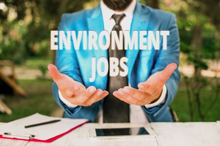 Text sign showing Environment Jobs. Business photo showcasing jobs that contribute to preserve or restore the environment Man with opened hands in fron of the table. Mobile phone and notes on the table