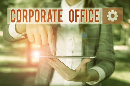 Handwriting text writing Corporate Office. Conceptual photo central location for planning and execution of a business Outdoor scene with business woman holds lap top with touch screen