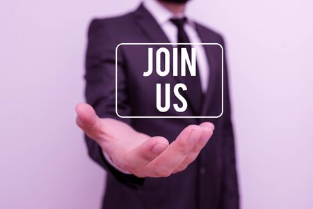 Writing note showing Join Us. Business concept for Register in community Team or blog Sign up at social media Male human with beard wear formal working suit clothes hand Stock Photo