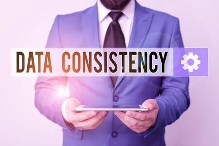 Text sign showing Data Consistency. Business photo text data values are the same for all instances of application Businessman in blue suite with a tie holds lap top in hands Foto de archivo - 135400067