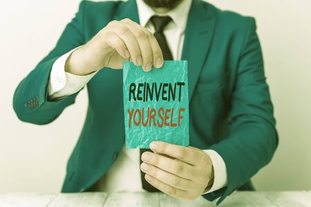 Conceptual hand writing showing Reinvent Yourself. Concept meaning to do something differently from before Change behavior Man holds empty paper with copy space in front of him Space