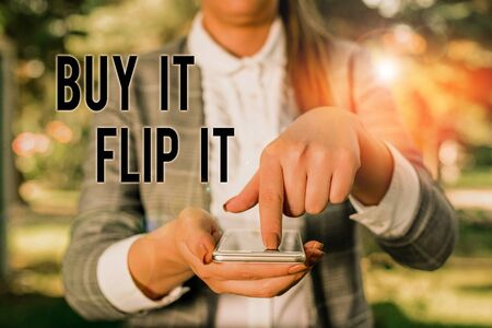 Word writing text Buy It Flip It. Business photo showcasing Buy something fix them up then sell them for more profit Woman in grey suites holds mobile phone Stock fotó