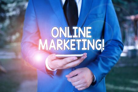 Conceptual hand writing showing Online Marketing. Concept meaning leveraging web based channels spread about companys brand Businessman in blue suite stands with mobile phone in hands