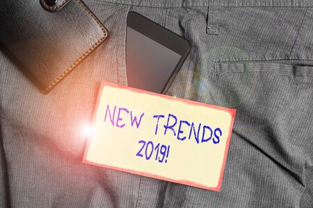 Handwriting text writing New Trends 2019. Conceptual photo general direction in which something is developing Smartphone device inside trousers front pocket with wallet and note paper