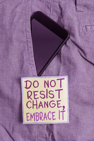 Text sign showing Do Not Resist Change Embrace It. Business photo text Be open to changes try new things Positive Smartphone device inside formal work trousers front pocket near note paper Reklamní fotografie