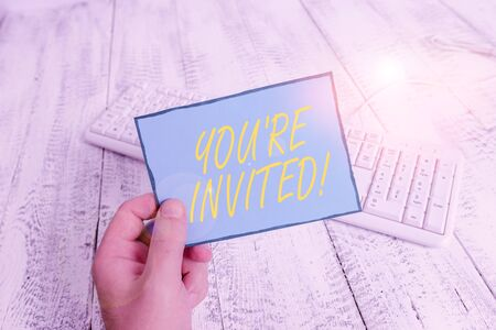 Writing note showing You Re Invited. Business concept for make a polite friendly request to someone go somewhere Man holding colorful reminder square shaped paper wood floor