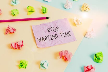 Writing note showing Stop Wasting Time. Business concept for advising demonstrating or group start planning and use it wisely Colored crumpled papers empty reminder blue yellow clothespin