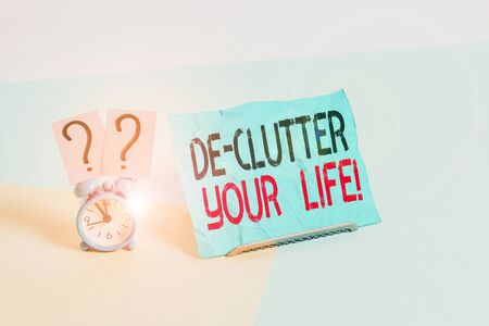 Conceptual hand writing showing De Clutter Your Life. Concept meaning remove unnecessary items from untidy or overcrowded places Alarm clock beside a Paper sheet placed on pastel backdrop