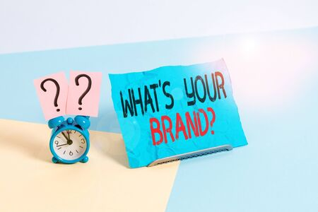 Conceptual hand writing showing What S Your Brand Question. Concept meaning asking about product logo does or what you communicate Alarm clock beside a Paper sheet placed on pastel backdrop Foto de archivo