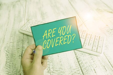 Writing note showing Are You Covered Question. Business concept for asking showing if they had insurance in work or life Man holding colorful reminder square shaped paper wood floor
