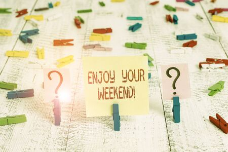 Writing note showing Enjoy Your Weekend. Business concept for wishing someone that something nice will happen at holiday Crumbling sheet with paper clips placed on the wooden table