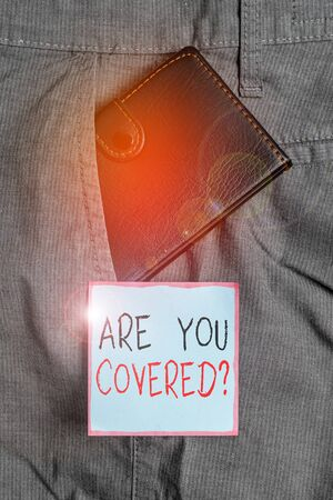 Writing note showing Are You Covered Question. Business concept for asking showing if they had insurance in work or life Small wallet inside trouser front pocket near notation paper