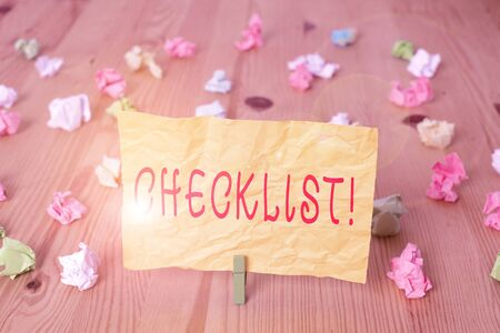Writing note showing Checklist. Business concept for list items required things be done or points considered Colored crumpled papers wooden floor background clothespin