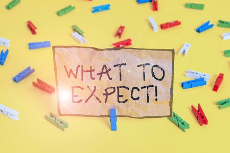 Handwriting text writing What To Expect. Conceptual photo asking about regard something as likely to happen occur Colored clothespin papers empty reminder yellow floor background office Stock Photo
