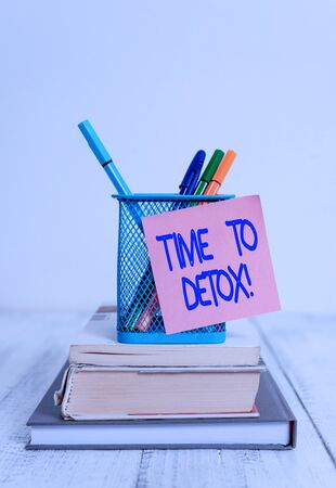 Word writing text Time To Detox. Business photo showcasing when you purify your body of toxins or stop consuming drug Stacked books pens metal holder sticky note lying vintage old wooden table Stock Photo
