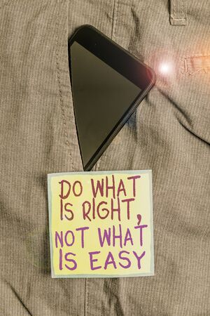 Text sign showing Do What Is Right Not What Is Easy. Business photo text willing to stand up for what is right Smartphone device inside formal work trousers front pocket near note paper Banco de Imagens