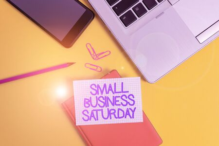 Conceptual hand writing showing Small Business Saturday. Concept meaning American shopping holiday held during the Saturday Laptop smartphone clip pencil paper sheet colored background