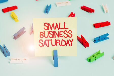 Word writing text Small Business Saturday. Business photo showcasing American shopping holiday held during the Saturday Colored clothespin papers empty reminder blue floor background office pin Фото со стока
