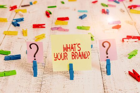 Writing note showing What S Your Brand Question. Business concept for asking about product logo does or what you communicate Crumbling sheet with paper clips placed on the wooden table Foto de archivo