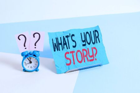 Conceptual hand writing showing What S Your Story Question. Concept meaning asking demonstrating about his past life actions events Alarm clock beside a Paper sheet placed on pastel backdrop Stock fotó