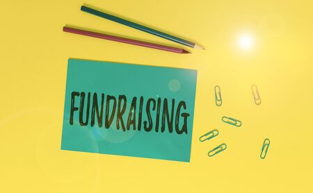Conceptual hand writing showing Fundraising. Concept meaning act of collecting or producing money for a particular purpose Blank paper sheet message reminder pencils clip colored background 版權商用圖片