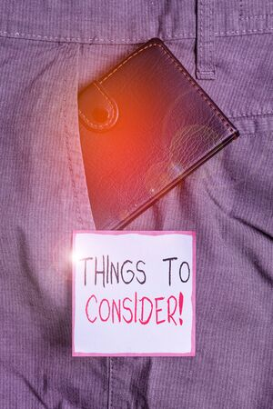 Writing note showing Things To Consider. Business concept for think about something carefully in order to make decision Small wallet inside trouser front pocket near notation paper