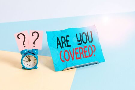 Conceptual hand writing showing Are You Covered Question. Concept meaning asking showing if they had insurance in work or life Alarm clock beside a Paper sheet placed on pastel backdrop