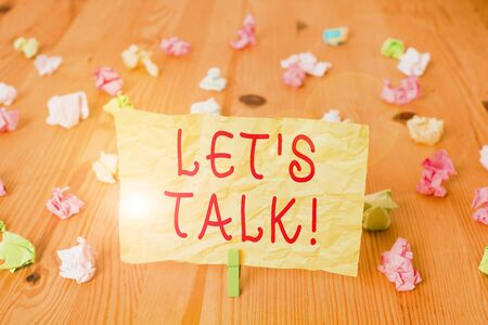 Writing note showing Let S Talk. Business concept for they are suggesting beginning conversation on specific topic Colored crumpled papers wooden floor background clothespin