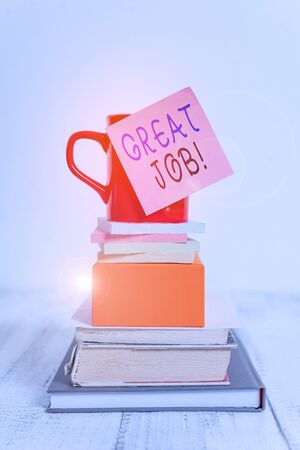 Conceptual hand writing showing Great Job. Concept meaning used praising someone for something they have done well Cup sticky note stacked note pads books box wooden table