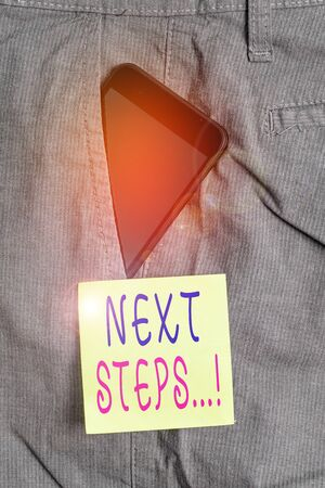 Word writing text Next Steps. Business photo showcasing something you do after you have finished doing first one Smartphone device inside formal work trousers front pocket near note paper