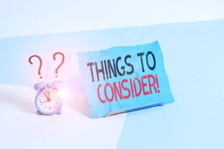 Conceptual hand writing showing Things To Consider. Concept meaning think about something carefully in order to make decision Alarm clock beside a Paper sheet placed on pastel backdrop