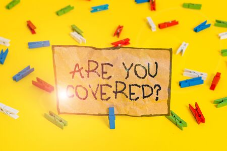 Handwriting text writing Are You Covered Question. Conceptual photo asking showing if they had insurance in work or life Colored clothespin papers empty reminder yellow floor background office
