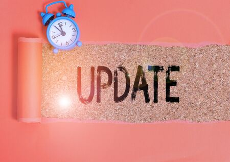 Conceptual hand writing showing Update. Concept meaning by adding new information or making corrections Up to date Alarm clock and torn cardboard on a wooden classic table backdrop