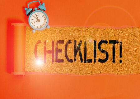 Conceptual hand writing showing Checklist. Concept meaning list items required things be done or points considered Alarm clock and torn cardboard on a wooden classic table backdrop Stockfoto
