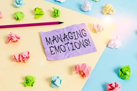 Writing note showing Managing Emotions. Business concept for ability be open to feelings and modulate them in oneself Colored crumpled papers empty reminder blue yellow clothespin